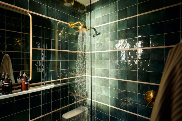 Corner of bathroom with running shower and tiled walls