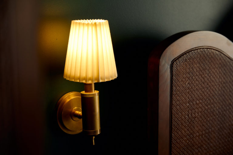 Closeup view of sconce and headboard