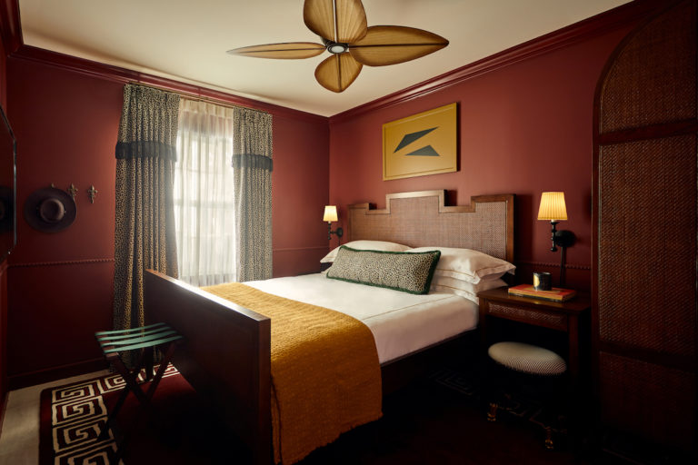 Hotel room with bed on area rug, ceiling fan, dresser and sunlight coming through window