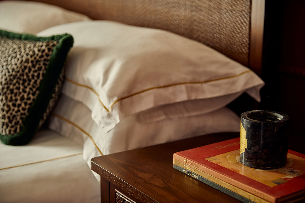 Closeup of books on nightstand table and pillows on bed in the background