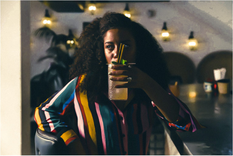 Woman with colorful striped long-sleeved blouse sipping a cocktail