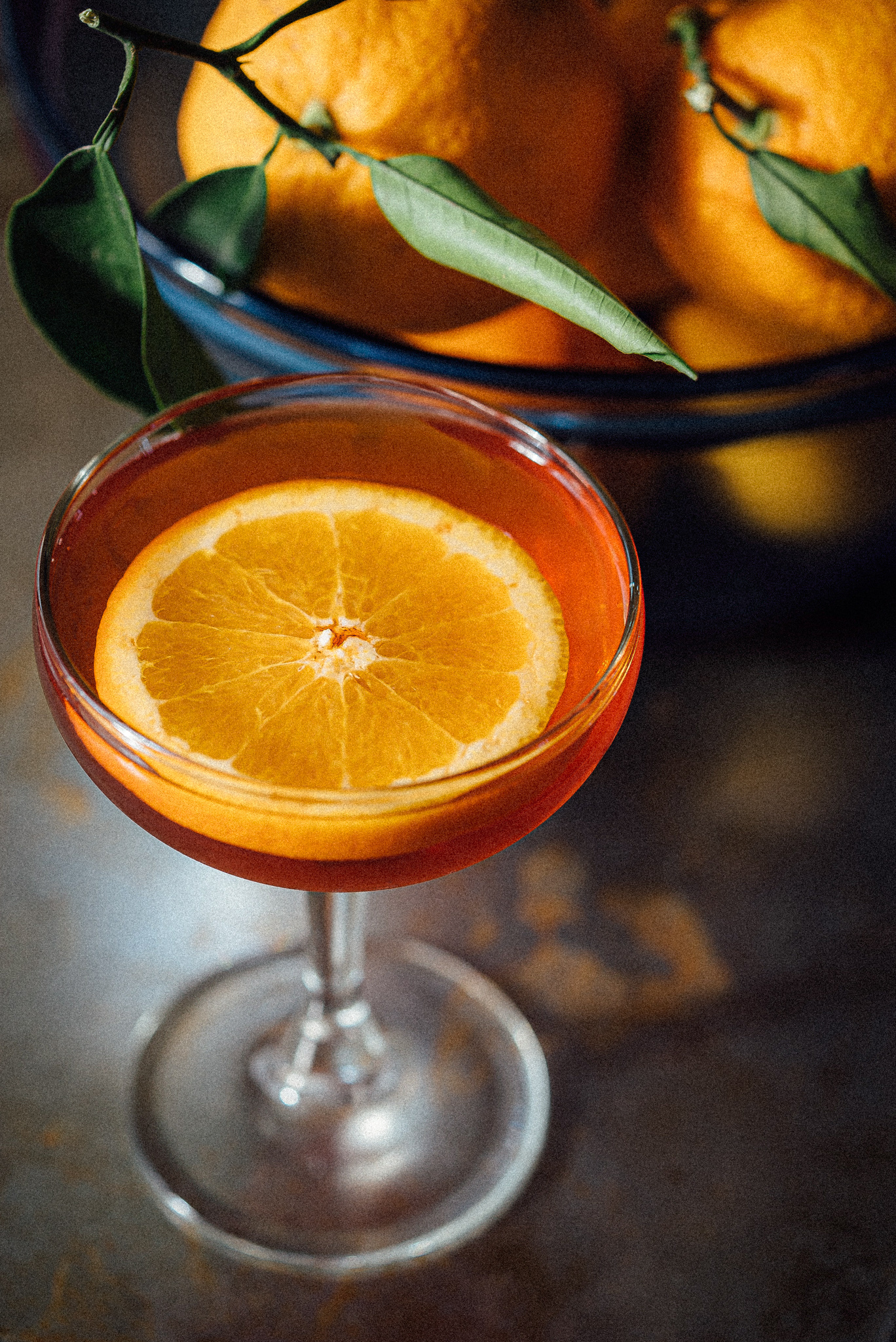 Closeup of cocktail with slice of orange next to a bowl of whole oranges with stems and leaves