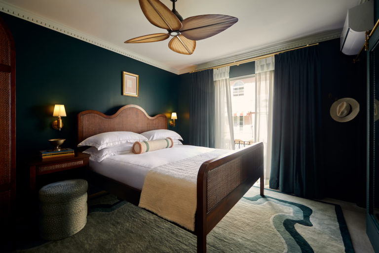 Hotel room bed, ottoman, nightstand, ceiling fan and view of buildings through open window