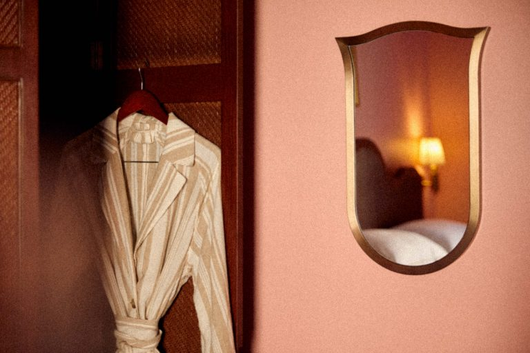 Bathrobe hanging on door and mirror frame shaped like a shield on the wall