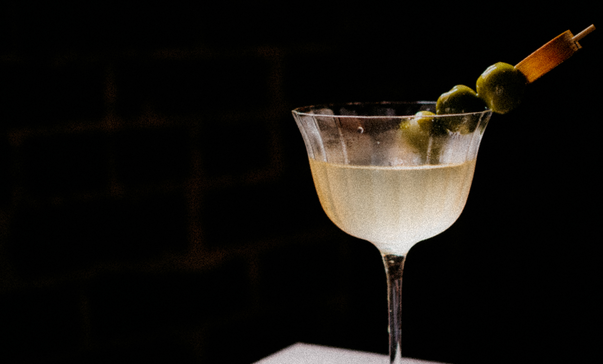 Cocktail with olives on a table with a dark background
